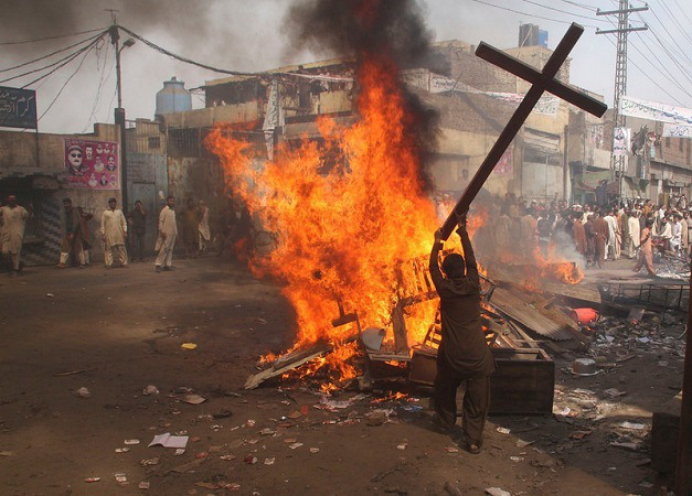 A demonstrator burns a cross during a protest in the Badami Bagh area of Lahore
